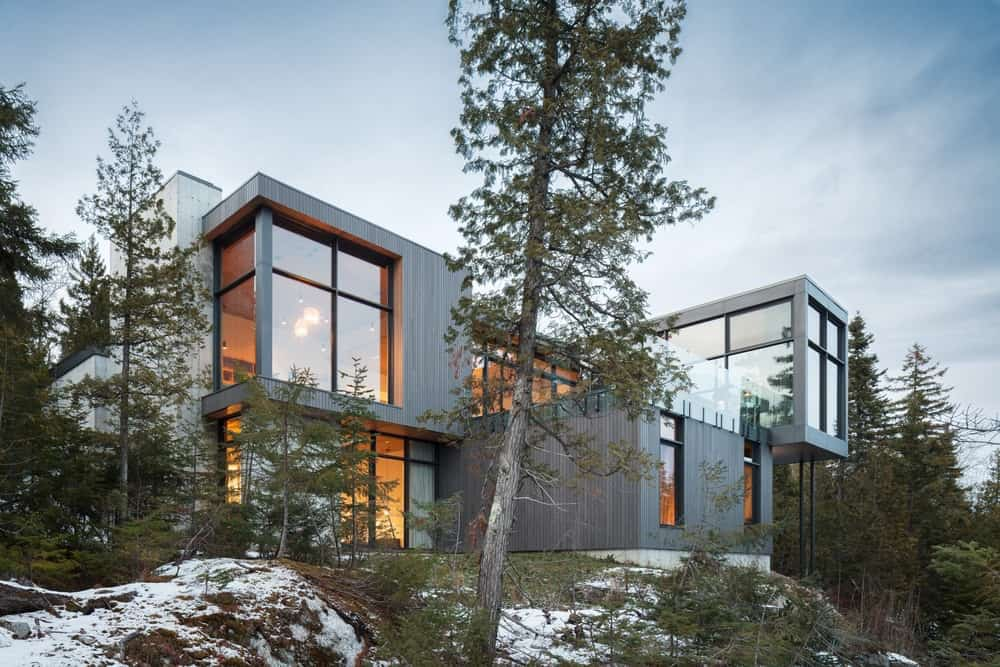 Modern house boasting a stylish exterior with glass windows and doors. The surroundings offer healthy greenery, while the earth is covered in snow.