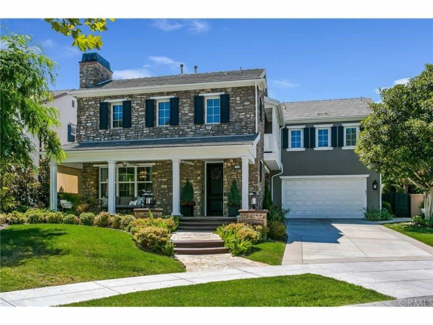 This house features a gray stone exterior along with a garage. It has well-maintained frontyard with beautiful plants and lawns.