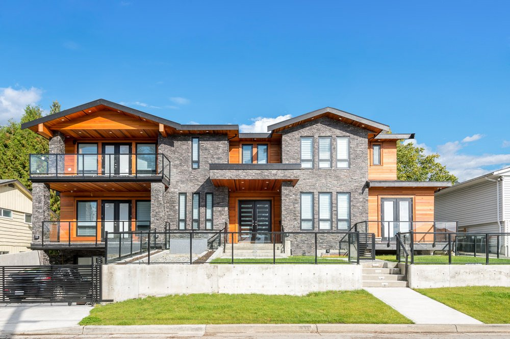 Modern house with a stunning exterior design. It has a balcony and a terrace, both featuring glass railings. It also has a nice gated garage and a beautiful front yard.