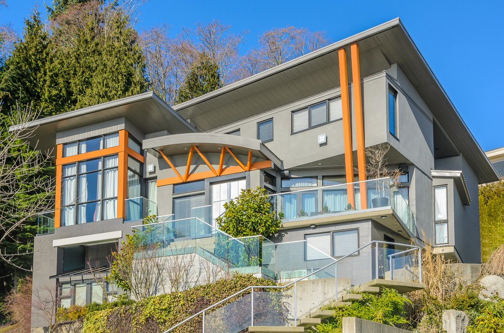A modern house with a gray exterior with a wood-tone accent. It has glass railings on its stairways and balcony areas. It also has a backyard with a nice set of amenities.