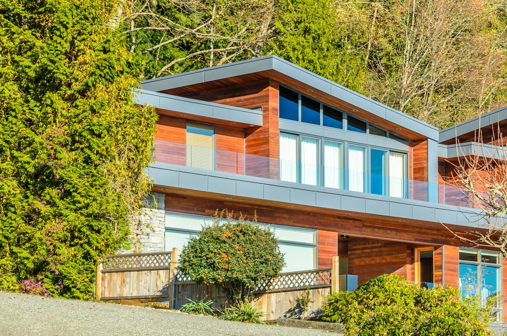 A look at this home's magnificent exterior design with a large balcony area featuring a glass railing. The property is surrounded by mature trees.