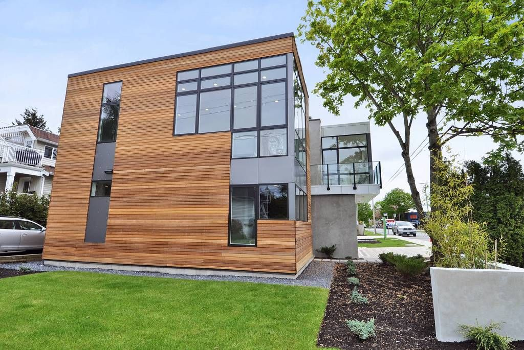 A focused look at this home's wood-tone exterior with glass windows. In its backyard sits a well-maintained lawn area, along with a small garden area.