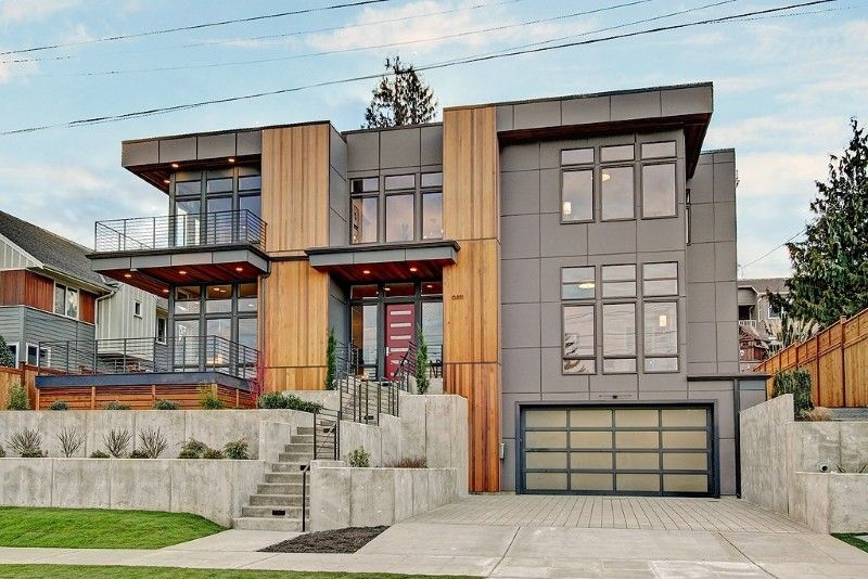 Modern house with a nice gray and wood-tone exterior design. The house offers balcony areas and a garage, along with a garden area.