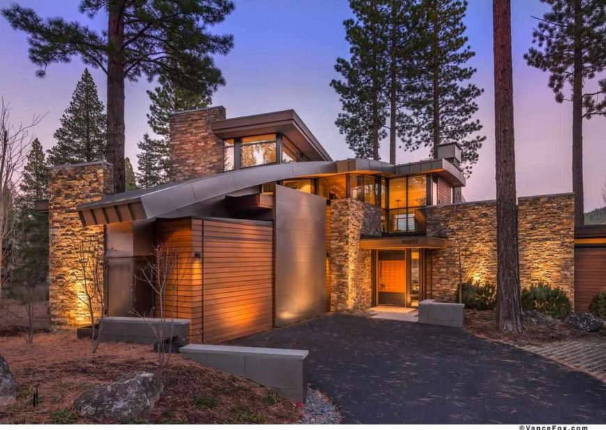 A modish house set in the woods. It has a stylish exterior design and a warm interior lighting. It has a nice driveway and other outdoor amenities surrounded by tall and mature trees.