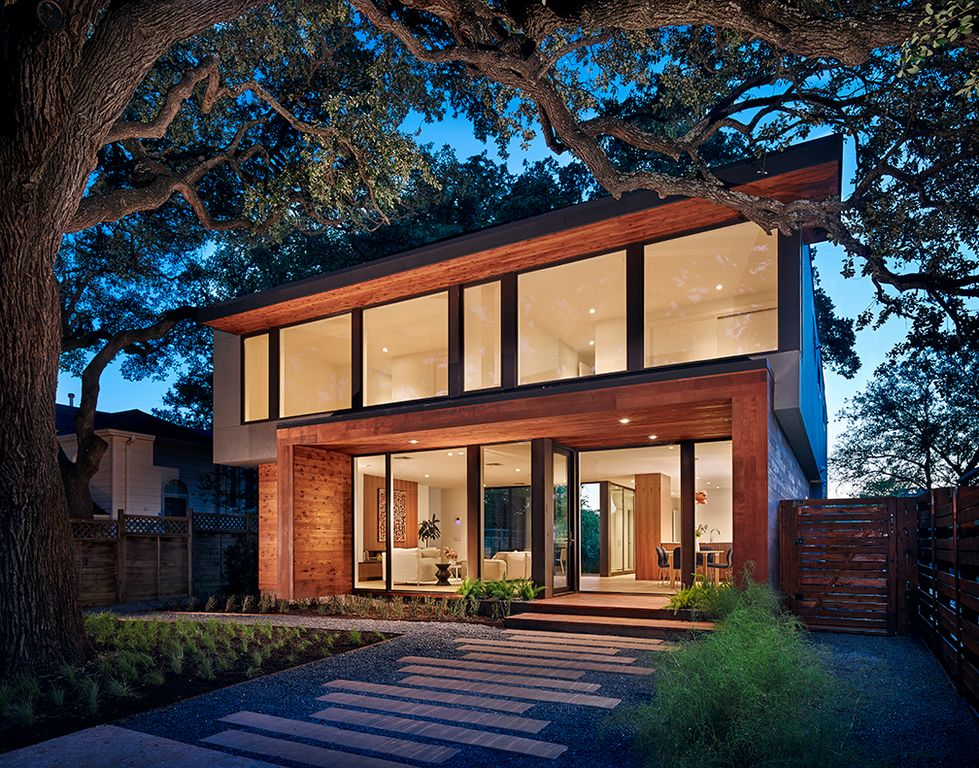 Modern house boasting a wood-tone exterior and glass windows and doors. It also offers a gorgeous walkway surrounded by plants and trees.