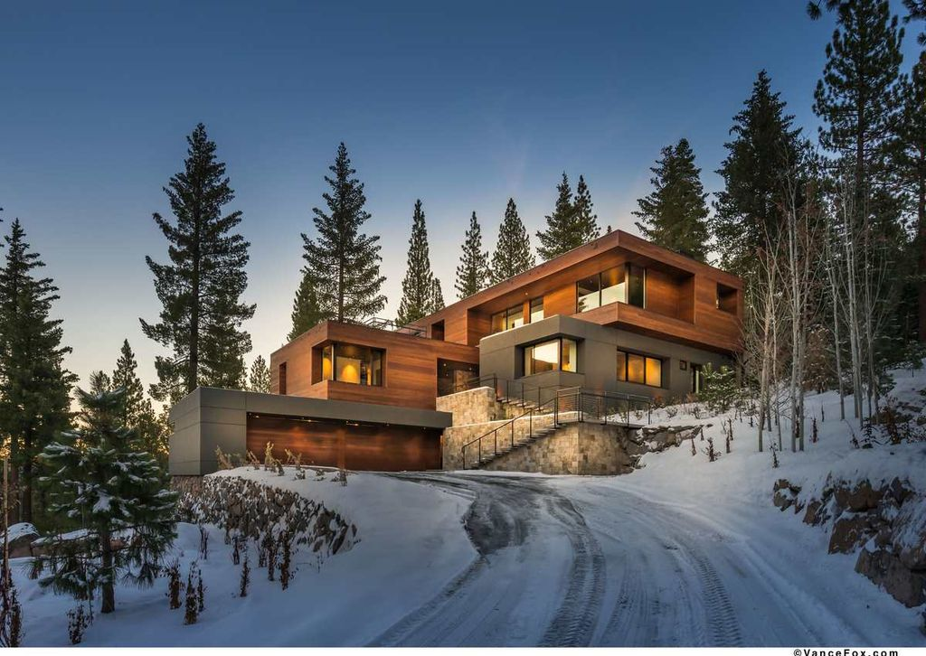 A contemporary house set in the woods. It has a very attractive exterior design surrounded by tall and mature trees. It has a wide driveway and a large garage.