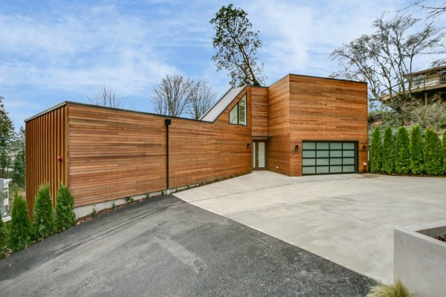 A house with a wood-tone exterior and has a very modish interior. It offers a wide driveway and garage, along with healthy plants and trees.