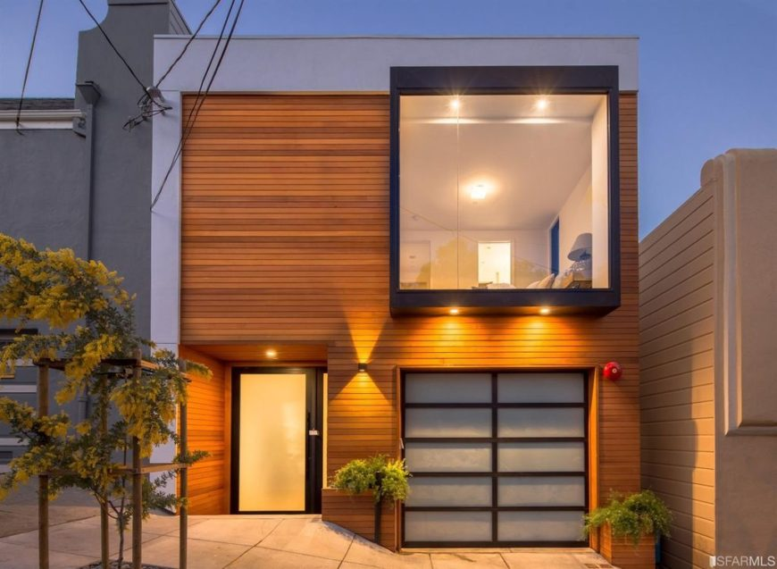 A closer look at this house's gray and wood-tone exterior with glass windows and doors.