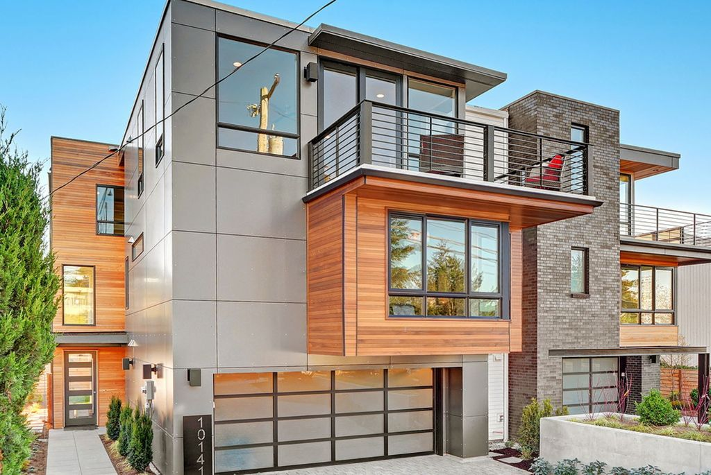 A look at this modern house with a stylish exterior design. It offers balconies and has a wide driveway, along with a small garden area.