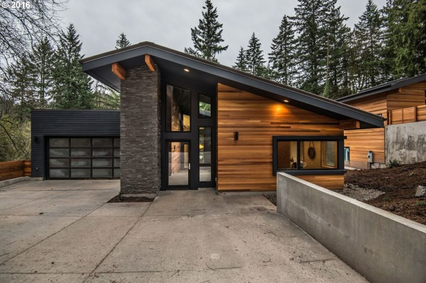 Contemporary house with a striking exterior design and has a concrete driveway. The property is surrounded by mature and tall trees.