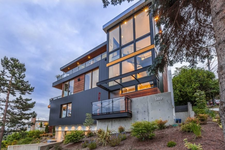 A contemporary house boasting a modish and stylish exterior with glass windows and doors. The home also offers a nice outdoor areas along with some balconies and terraces.