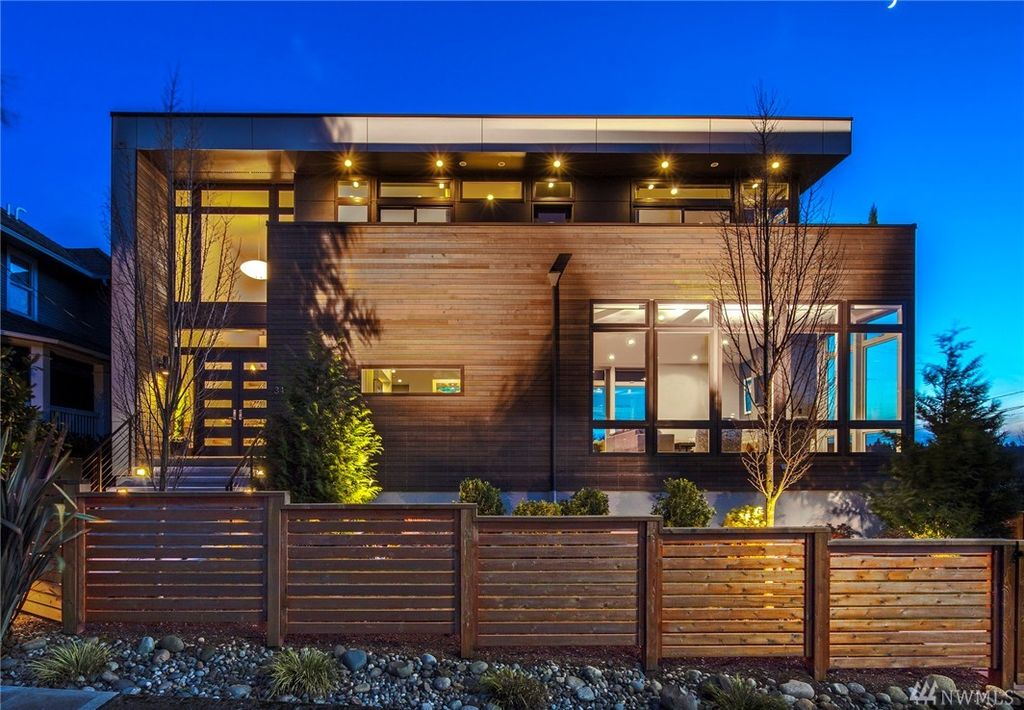 This house boasts a very stylish wood-tone exterior with a wooden fence. The home offers a gorgeous garden and outdoor areas.