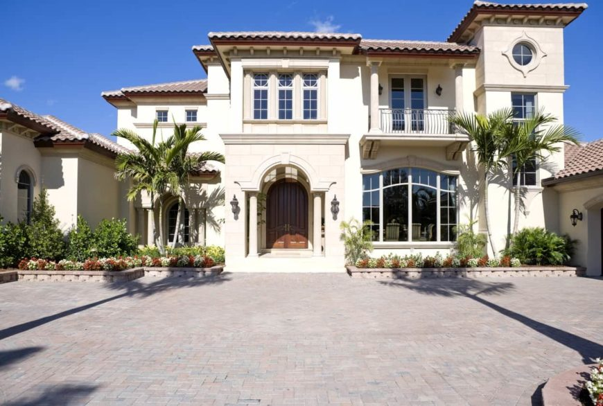 A large mansion boasting a beautiful exterior. The grounds offer well-placed plants and trees, along with a spacious driveway leading to the home's garage.