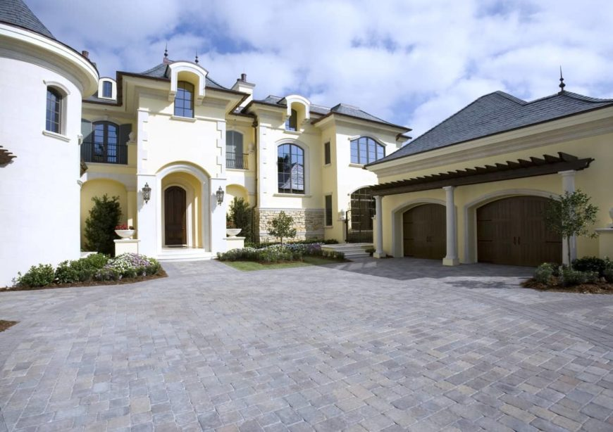 This mansion boasts spacious driveway with a large garage. The house exterior looks absolutely gorgeous. The plants are well placed as well.
