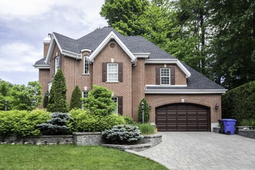 This house boasts a fancy brown exterior with a gray roof. It features a garage and a lawn area, along with green plants and trees surrounding the courtyard.