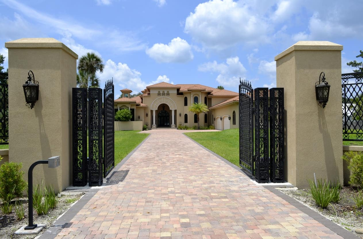 A gated mansion with iron and concrete fence securing the property. The house feature healthy lawn areas, both in frontyard and in the backyard. The home's outdoors also offer many amenities.