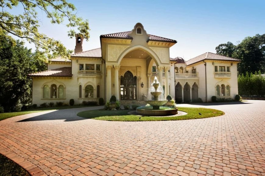 A Spanish-style mansion boasting a wide brick courtyard with a fountain in the center, surrounded by circular lawns. The property features a backyard with many outdoor amenities as well.