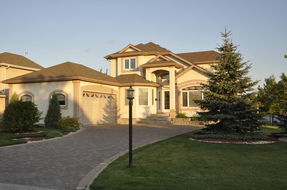 A peaceful mansion boasting a fine driveway surrounded by well-maintained lawn areas, plants and trees.