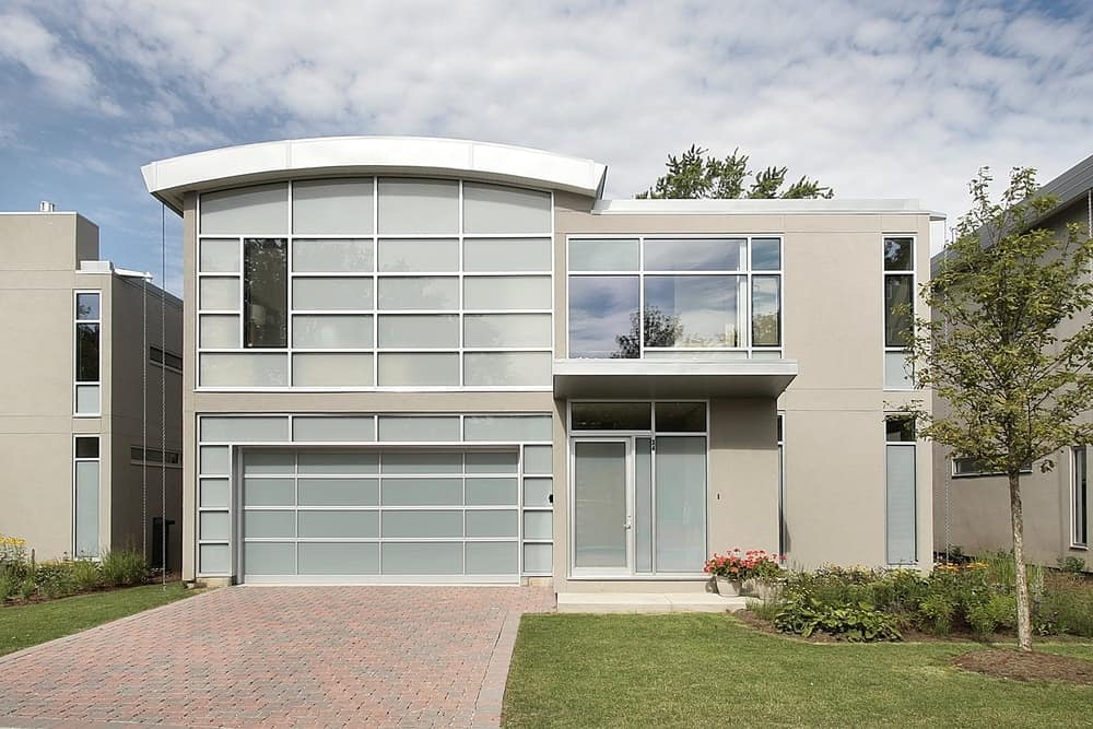 This house boasts a contemporary exterior look with a stylish garage and a driveway. There's a small lawn and garden area as well.