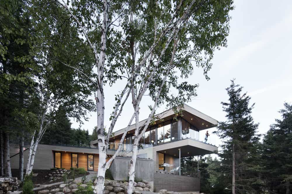 Contemporary home with a stylish modern exterior, featuring glass walls and windows, along with glass railings. The property is surrounded by gorgeous greenery.