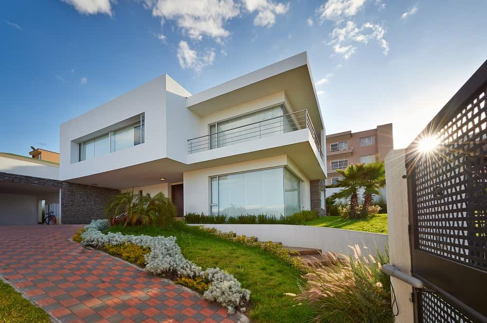 Large modern house with a gorgeous exterior and a stylish driveway, along with beautiful lawns and plants laid on the side.