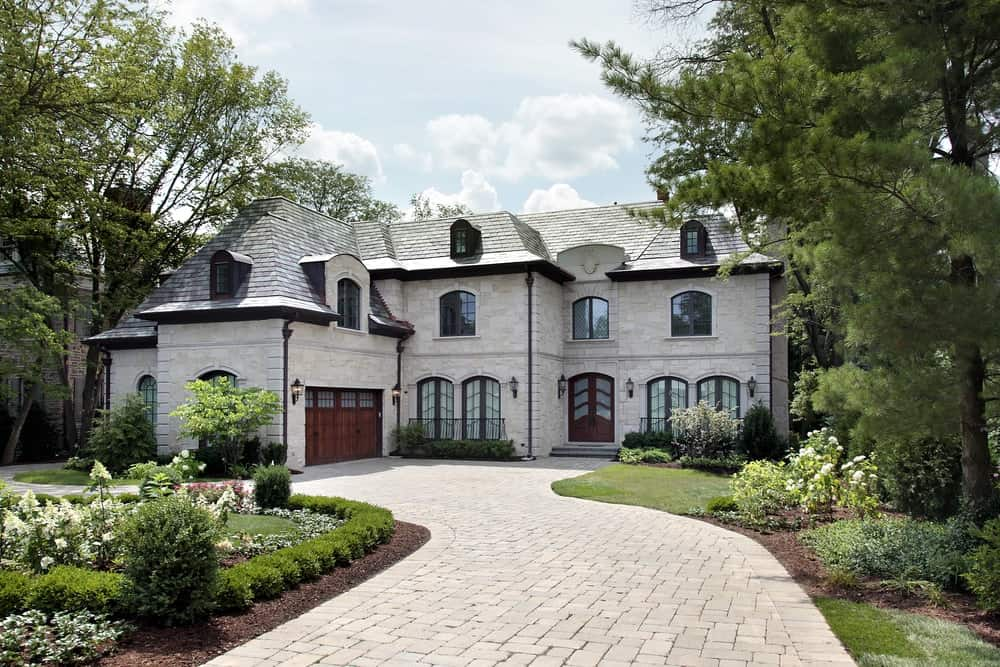 This house has a gray exterior and a black roof, along with glass windows. The driveway has a garden set on its side, along with tall and mature trees.