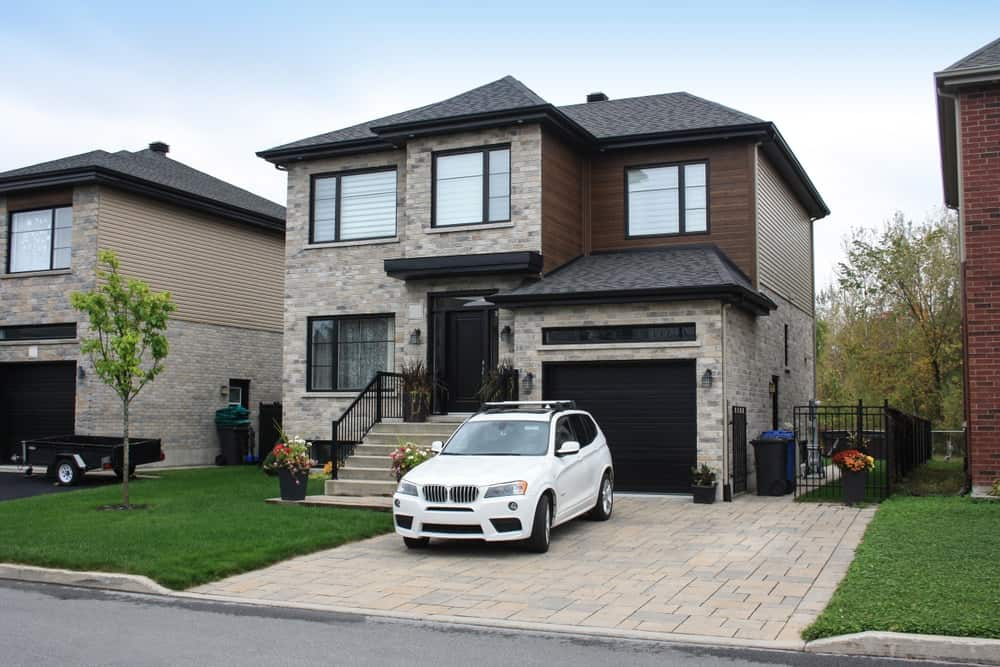 This house features a modish and stylish exterior along with glass windows and a small garage and driveway. It has a small backyard as well.