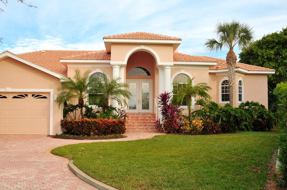 This gorgeous home has a beige exterior and orange roof. It has a nice driveway, along with a lawn area and a garden area.