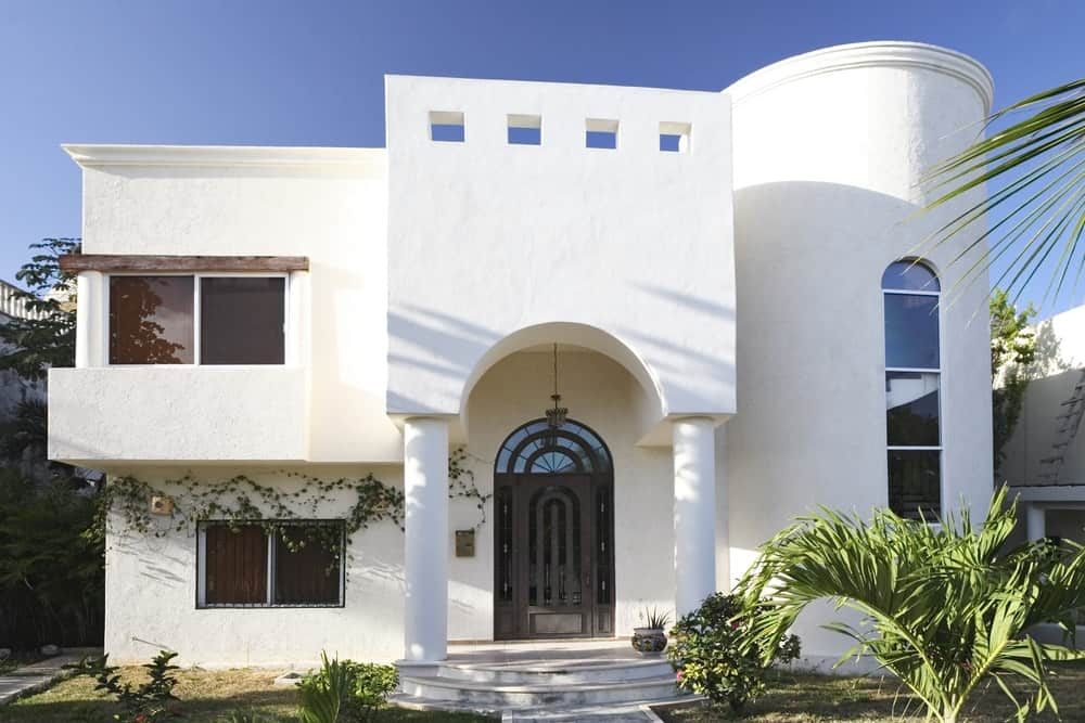 A closer look at this modish house's white and beautiful exterior. The home has a peaceful garden with lots of greens.