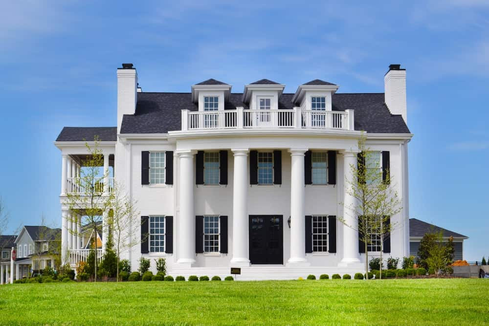 A stunning white mansion with lavish outdoor areas featuring well-maintained lawns, a beautiful garden and an outdoor dining and kitchen.