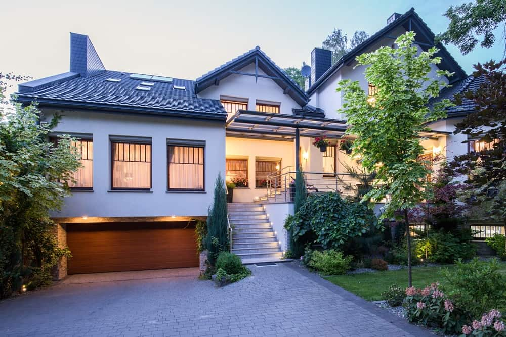 A lovely white exterior featuring a nice garage and a fancy garden area with beautiful flowers and plants.