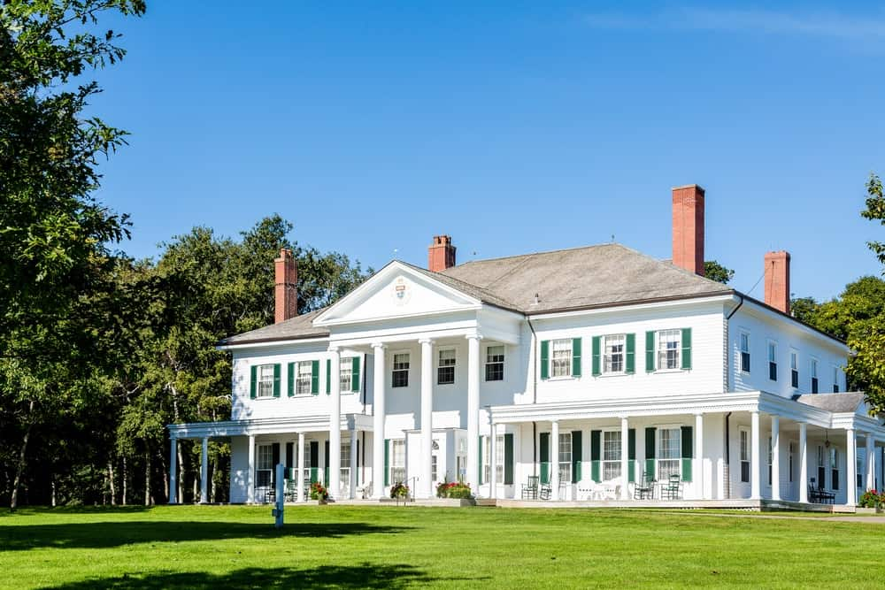 A beautiful mansion boasting a clean white exterior and a massive lawn area that is well-maintained. The property is surrounded by mature and tall trees.