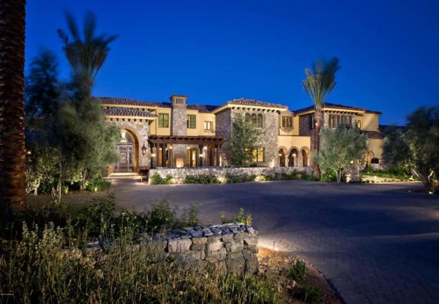 A large mansion boasting a wide courtyard with a large driveway surrounded by mature and tall trees. The property also has an outdoor pool, patio and garden.