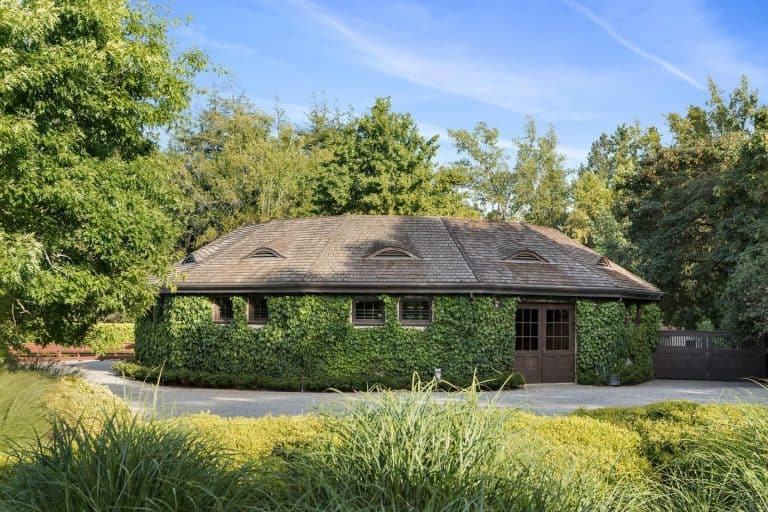 This custom-made house boasts a very interesting exterior surrounded by greens and tall and mature trees. It also has a nice driveway leading to the garage.