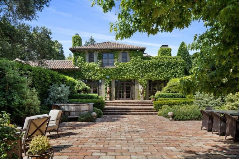 This property features a brick walkway surrounded by the beautiful greenery. There's a patio area and an outdoor dining. The house's exterior looks absolutely interesting.