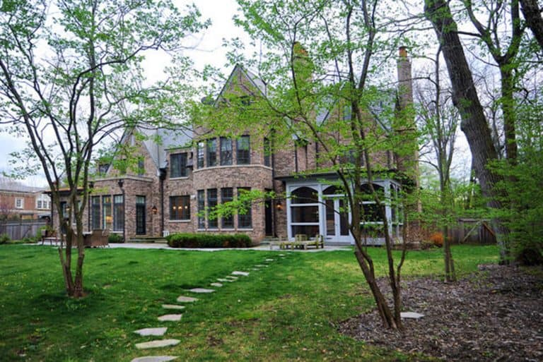 This house boasts a striking exterior design and has a gorgeous garden area with lawns area and a walkway surrounded by the trees.