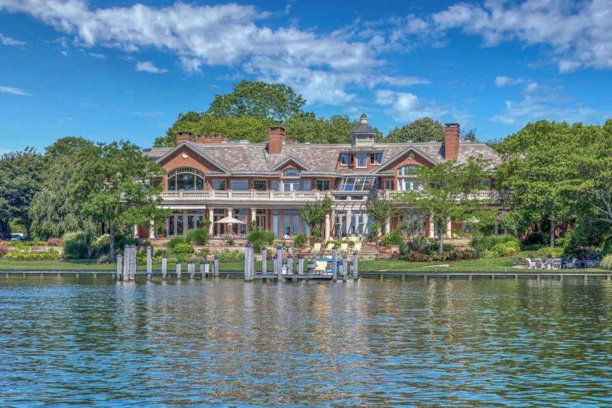 A large house with stylish exterior that looks modish. It is surrounded by mature trees and lawn areas. The area also has a nice view of the lake.