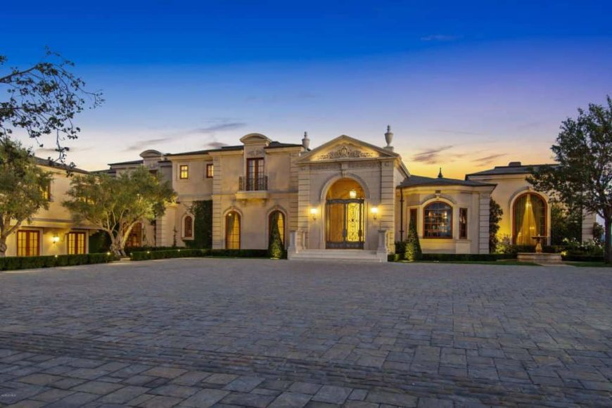 A large mansion boasting a very spacious courtyard with well-placed trees and plants. The home's exteriors and interiors are very well designed as well.
