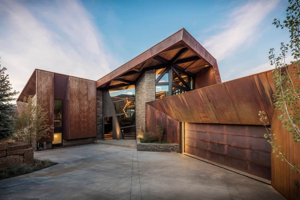 A contemporary house boasting a custom brown exterior with a spacious courtyard with concrete grounds.