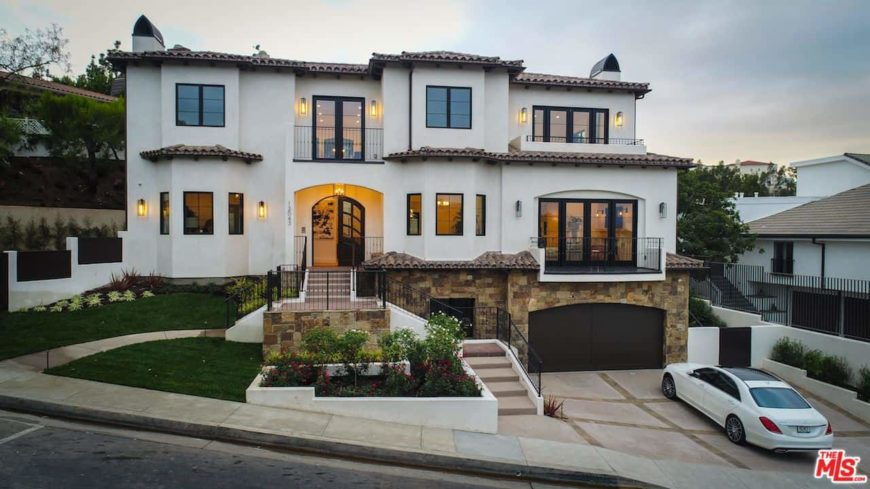A striking celebrity home with a white exterior and glass windows and doors. It offers a nice garage and a beautiful small front yard garden area.
