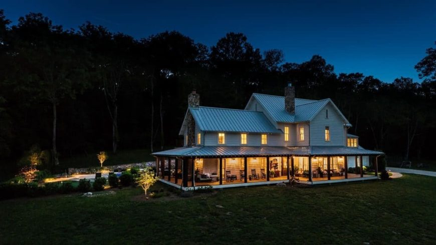 This home offers a warm interior illuminating the space surrounded by the dark woods. The home boasts a wide lawn area and a stunning outdoor swimming pool at the back. It also has a deck area with a patio.