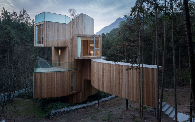 This contemporary house boasts a breathtaking exterior design surrounded by silent and peaceful woods.