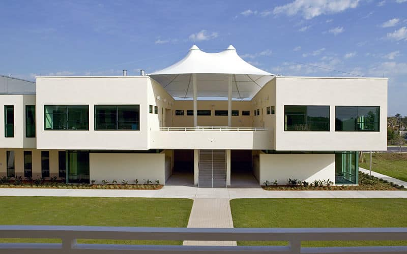 Modern large house with a white exterior and glass windows. It has spacious outdoor areas featuring a nice walkway surrounded by beautiful lawn areas.
