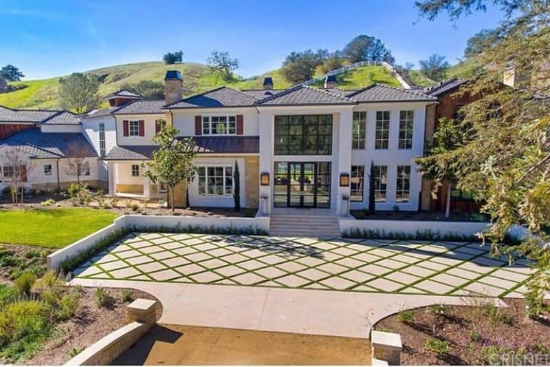 A glamorous large house with a beautiful white exterior and glass windows and doors. The backyard is just so beautiful with its lawns, gardens and trees.