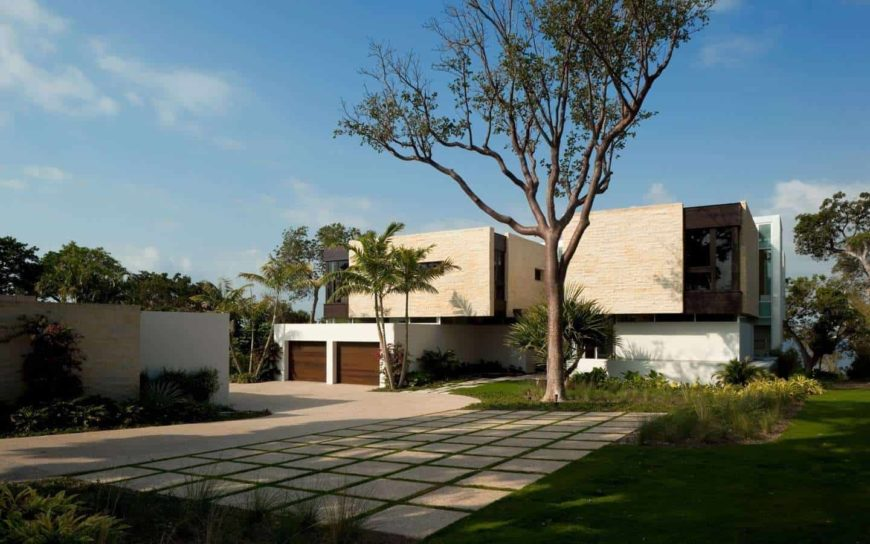 A large modern house with a fancy exterior designs. It offers a nice driveway, a gorgeous walkway and a lovely garden and lawns area.