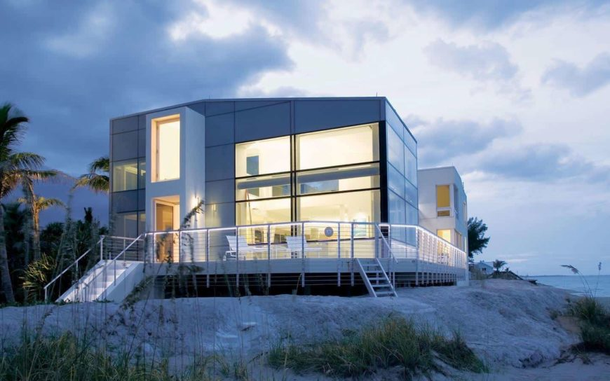 A modern large house on the beach, featuring a stunning exterior design with multiple large glass windows and doors. It has a deck with a patio as well.