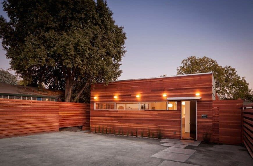 A modern house boasting a very attractive wood-tone exterior with warm outdoor lighting. It has a wide backyard with concrete grounds and has a walkway.