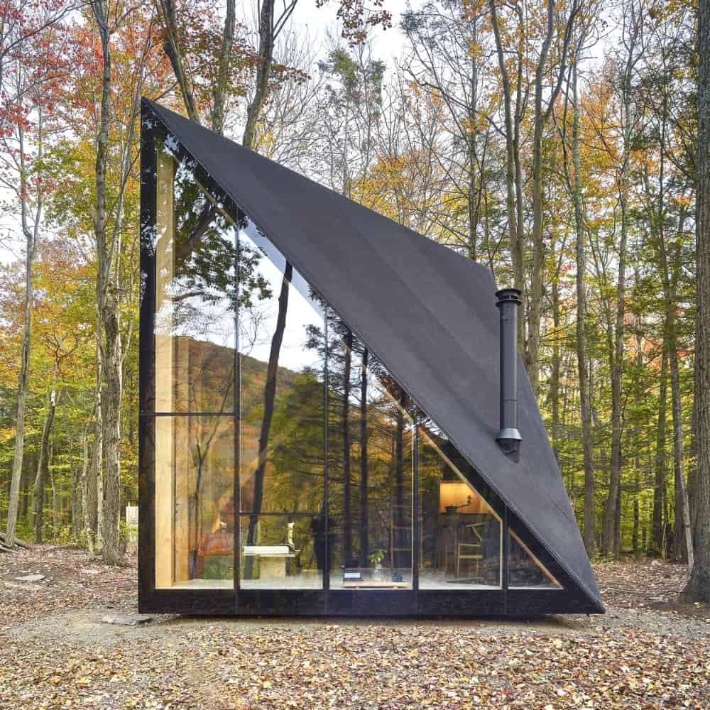 A contemporary house with a stunning exterior, featuring glass walls and windows and a black roof. The home is surrounded by mature trees.