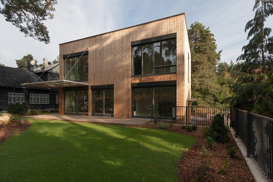 A modish-looking house with a wooden exterior and glass windows and doors. The house offer a deck and a large lawn and garden areas.