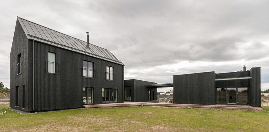 This house features a stylish black exterior along with a deck and has a wide lawn area.